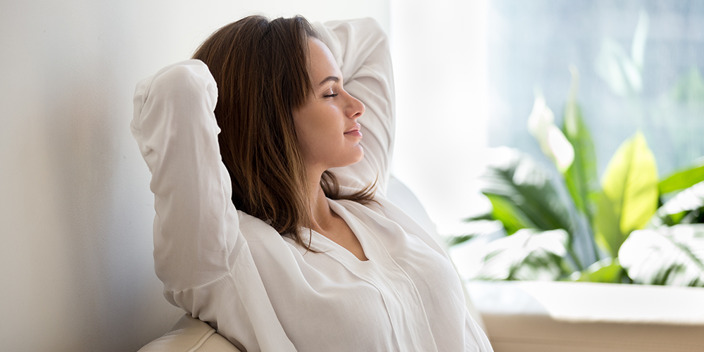 Woman on couch breathes easier with helpful indoor air quality solutions.